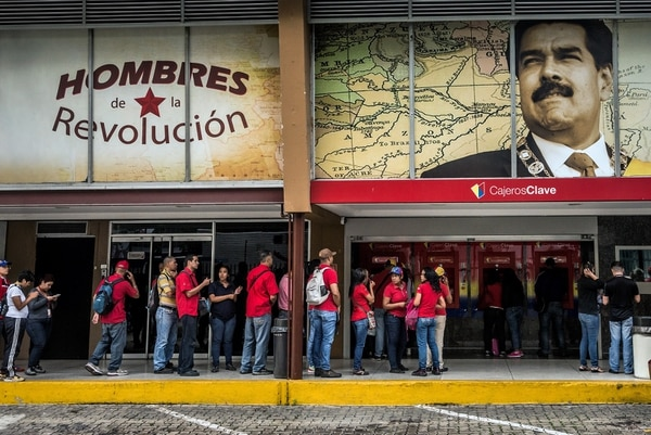 Beneath a photo of Venezuela's president, Nicolas Maduro, people wait in a long line in Caracas to get bills of the new currency, sovereign bolívar, available for the first time at banks on Tuesday, Aug. 21, 2018. Sign at left reads