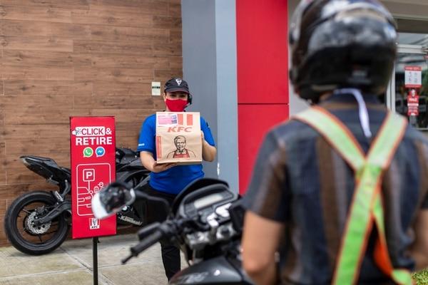 En sus restaurantes de mayor tamaño, KFC habilitó un espacio de parqueo exclusivo para la entrega de pedidos, sin necesidad de bajarse del vehículo, entrar al restaurante o hacer fila. Joselyn Ferrán es una de las colaboradoras encargadas de esa tarea en el KFC de Coronado. Fotografía: José Cordero