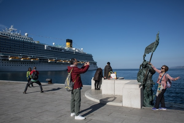 Tourists in Trieste, Italy, March 8, 2019. A new cruise ship, built in nearby shipyards expressly for Chinese passengers, is docked behind them. Despite American objections, Italy is set to become the first Group of 7 nation to participate in China's vast One Belt, One Road infrastructure project. For China, having a toehold in one of Europe's historic ports would bring favorable customs conditions, a faster trade route to the heart of the Continent and direct access to railroads for moving its goods into the European Union. (Nadia Shira Cohen/The New York Times)