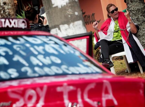 Virginia Moreira, propietaria dce un taxi, se encadenó afuera de la casa del presidente Luis Guillermo Solís, para exigir la suspensión de Uber en Costa Rica. El hecho se dio en octubre del 2016. Fotografía: José Cordero.