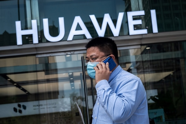 En esta foto de archivo tomada el 25 de mayo de 2020, un hombre pasa frente a una tienda del gigante chino de telecomunicaciones Huawei en Beijing. Fotografía: AFP.