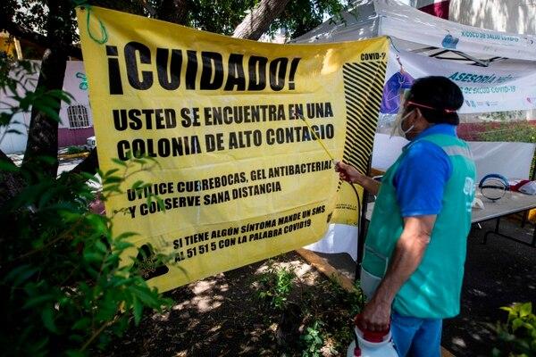 Un trabajador diseña una pancarta en un stand que brinda pruebas para la detección de COVID-19 en medio de la pandemia del nuevo coronavirus, en la Ciudad de México el 7 de agosto de 2020. - América Latina y el Caribe superó a Europa el viernes para convertirse en la región más afectada. por muertes por coronavirus. En todo el mundo ha habido más de 715.000 muertes por el virus reportadas por primera vez en China a fines del año pasado. (Foto: Pedro PARDO / AFP)