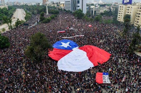 Aerial view of people demonstrating with a giant Chilean national flag against the government of Chilean President Sebastian Pinera in Santiago, on November 8, 2019. - Unrest began in Chile last October 18 with protests against a rise in transport tickets and other austerity measures that descended into vandalism, looting, and clashes between demonstrators and police. (Photo by MARTIN BERNETTI / AFP)