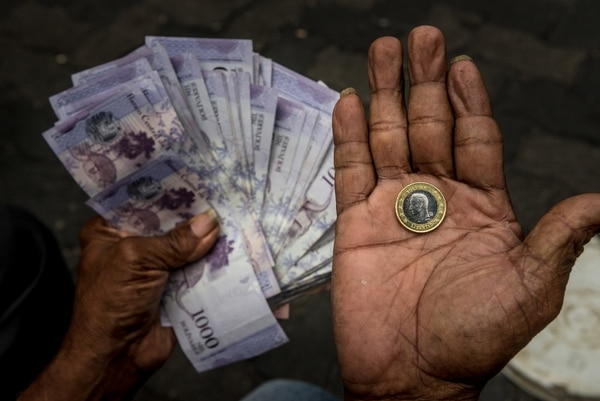 A fruit vendor holds one coin of the new sovereign bolívar, right, with its value in the old currency in his other hand, in Caracas, Venezuela, Aug. 21, 2018. An economic plan to fix the crumbling economy left Venezuelans uncertain of what their money was worth and afraid of more job losses. (Meridith Kohut/The New York Times)