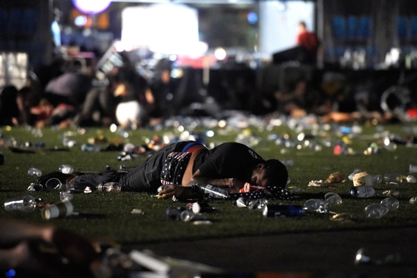 TOPSHOT - LAS VEGAS, NV - OCTOBER 01: (EDITORS NOTE: Image contains graphic content.) A person lies on the ground at the Route 91 Harvest country music festival after apparent gun fire was heard on October 1, 2017 in Las Vegas, Nevada. There are reports of an active shooter around the Mandalay Bay Resort and Casino. David Becker/Getty Images/AFP / AFP PHOTO / GETTY IMAGES NORTH AMERICA / David Becker
