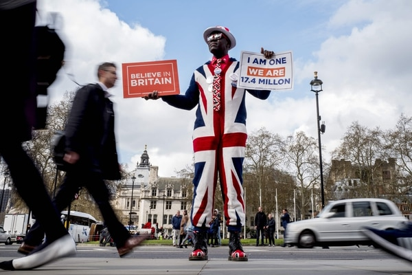 A pro-Brexit campaigner wears the Union flag colours and holds placards as he demonstrates near the Houses of Parliament in central London on April 3, 2019. - Prime Minister Theresa May was to meet on Wednesday with the leader of Britain's main opposition party in a bid to thrash out a Brexit compromise with just days to go until the deadline for leaving the bloc. (Photo by Tolga Akmen / various sources / AFP)