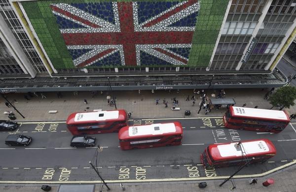 Peatones caminan por Oxford Street donde se colocó una bandera británica en la fachada de uno de los grandes almacenes en Londres (Reino Unido).