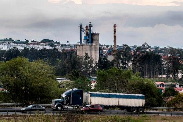 Un camión y automóviles pasan por una fábrica en San José. El Plan Nacional de Descarbonización presentado por el presidente costarricense Carlos Alvarado apunta a transformar la economía con la base de una matriz eléctrica de recursos renovables para 2050. Fotografía: AFP.
