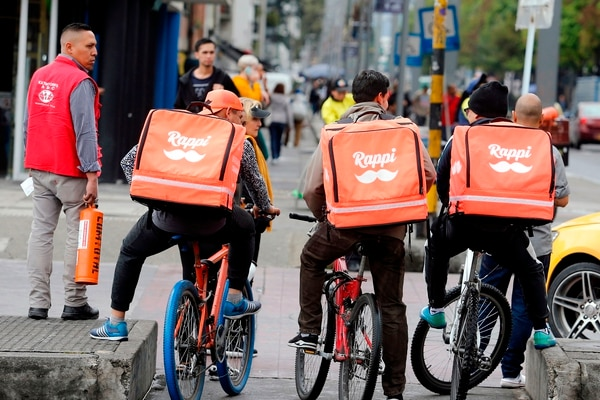 (FILES) In this file photo taken on October 25, 2018 Venezuelan nationals working as bicycle couriers, for Colombian online delivery company