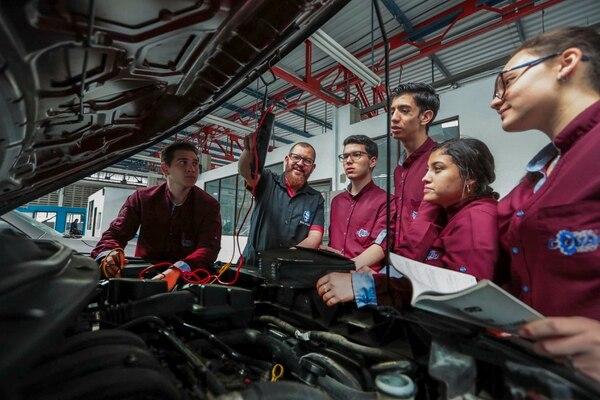 Kevin Solano, mentor de educación dual, da una clase práctica de mecánica automotriz a estudiantes del Colegio Vocacional de Artes y Oficios (Covao), en Cartago. Fotografía: Alonso Tenorio.