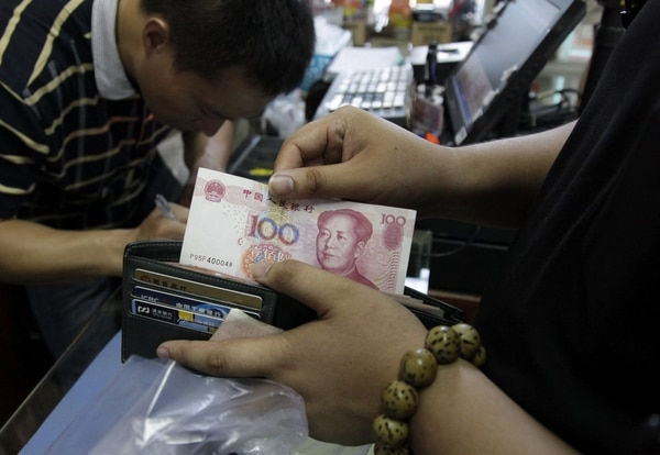 Un cliente saca un billete de 100 yuanes en una tienda de Pekín, China, hoy, 13 de agosto de 2015. El Banco Popular de China (central) dio hoy por concluido el ajuste en el valor del yuan, después de rebajar durante tres jornadas consecutivas el tipo de cambio de referencia de la divisa asiática.