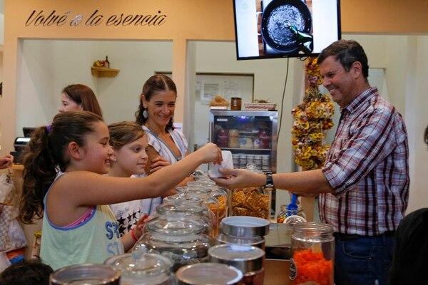 Jorge Hidalgo, esposo de Roxana Garita, entrega dulces a la niña Maripaz Herrera (izquierda). Con ella, la niña Andrea Rojas y su mamá Laura Angulo. (Foto Mayela López)