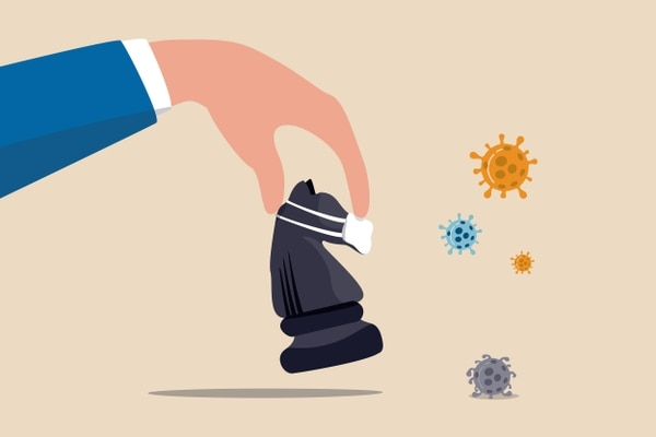 Business strategy in crisis, solution or idea to pass Coronavirus COVID-19 pandemic concept, investor or company owner hand holding chess knight wearing face mask to fight with Coronavirus pathogen.