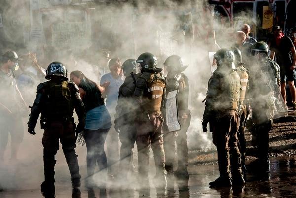 La policía antidisturbios y los manifestantes son vistos en medio de gases lacrimógenos después de una protesta contra el gobierno del presidente chileno, Sebastián Piñera, en Santiago, el 18 de diciembre de 2019. Fotografía: AFP.