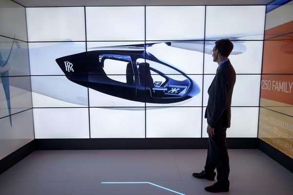 A man poses alongside screens presenting the Rolls-Royce EVTOL air taxi concept during the Farnborough Airshow, south west of London, on July 16, 2018. / AFP PHOTO / Tolga AKMEN