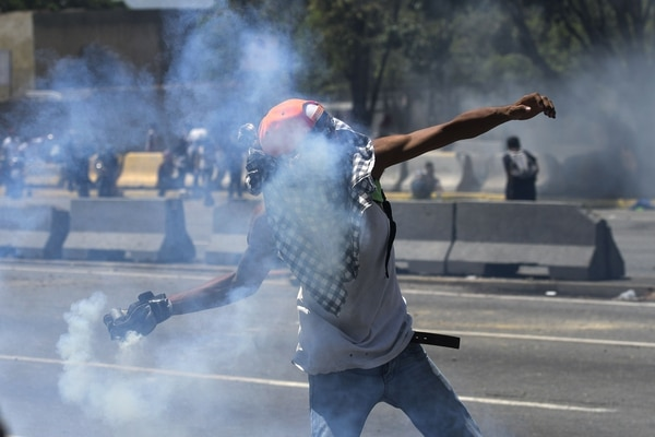 "An opposition demonstrator throws a tear gas canister during clashes with soldiers loyal to Venezuelan President Nicolas Maduro after troops joined opposition leader Juan Guaido in his campaign to oust Maduro's government, in front of La Carlota military base in Caracas on April 30, 2019. - Guaido -- accused by the government of attempting a coup Tuesday -- said there was ""no turning back"" in his attempt to oust President Nicolas Maduro from power. (Photo by Matias DELACROIX / AFP)"