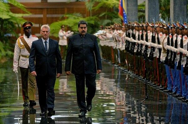 El presidente cubano, Miguel Díaz-Canel (a la izquierda), y su homólogo venezolano, Nicolás Maduro (derecha) revisan la guardia de honor en el Palacio de la Revolución, en La Habana, el 21 de abril de 2018.