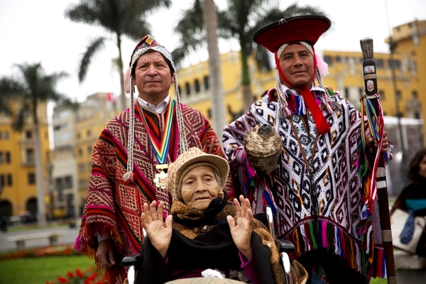 Maria Lucia Vargas, 86, poses for a picture with performers dressed as Quechua indigenous people outside the National Palace after Peru's newly sworn-in President Pedro Pablo Kuczynski entered with his cabinet in Lima, Peru, Thursday, July 28, 2016. Kuczynski assumed Peru's presidency Thursday with a Cabinet that shares his Ivy League, pro-business pedigree — a reliance on technocrats that could become a liability as he deals with an unfriendly congress and a resurgent left. (AP Photo/Rodrigo Abd)