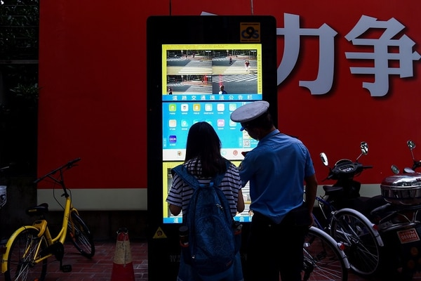 Un policía explica el funcionamiento de una pantallas de reconocimiento facial instalada en una intersección en Shánghai. Desde dispensadores de papel higiénico, restaurantes de comida rápida, aerolíneas y hasta la lucha contra el crímen, china está tomando la delantera en la tecnología de reconocimiento facial.