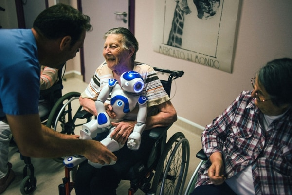 A patient sits with a robot named Zora at Jouarre, a nursing facility an hour outside Paris, on Aug. 30, 2018. It may not look like much — more cute toy than futuristic marvel — but this robot is at the center of an experiment in France to change care for elderly patients. (Dmitry Kostyukov/The New York Times)