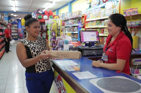 Yesilet Brown (izquierda) recibe un paquete de compras en línea de la venderora Viviana Martinez, en Leiton's Store de San José centro. Foto: Jeffrey Zamora