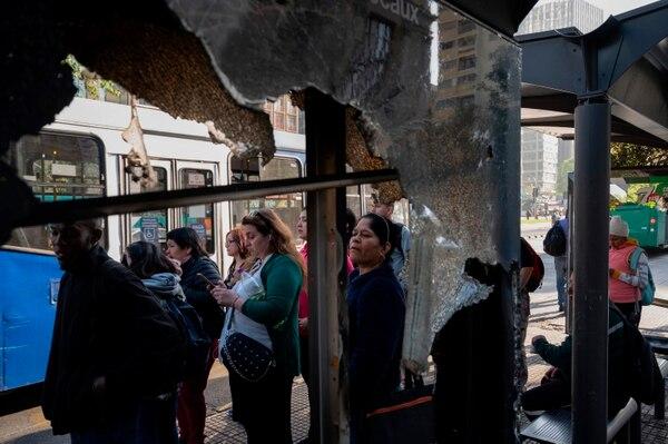 La gente espera tomar un autobús en Santiago, Chile, el 21 de octubre de 2019. Las protestas violentas, inicialmente contra un aumento en las tarifas del metro, estallaron por primera vez el viernes con muchas estaciones de metro atacadas, autobuses incendiados y semáforos destrozados mientras se saqueaban varios supermercados. Foto: AFP.