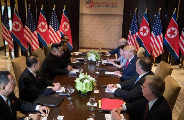 US President Donald Trump (3rd R) and North Korea's leader Kim Jong Un (3rd L) sit down with their respective delegations for the US-North Korea summit, at the Capella Hotel on Sentosa island in Singapore on June 12, 2018. Donald Trump and Kim Jong Un became on June 12 the first sitting US and North Korean leaders to meet, shake hands and negotiate to end a decades-old nuclear stand-off. / AFP PHOTO / SAUL LOEB