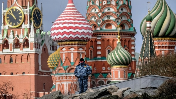 A security person stands guard at the Zaryadye park, with the Kremlin's Spasskaya tower and St. Basil's Cathedral seen on the background, in downtown Moscow on March 24, 2020. (Photo by Yuri KADOBNOV / AFP)