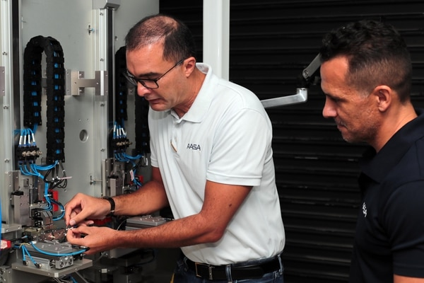 Erick Silesky (de blanco) y Juan Carlos Brenes revisan una de los equipos de automatización que fabrican en su compañía AASA. (Foto Alonso Tenorio)