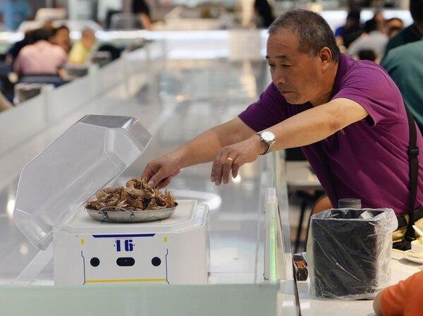 En esta fotografía del 30 de julio del 2018, se muestra a un hombre tomando su comida que fue servida por un robot. ROBOT.HE es un restaurante en Shanghai. AFP.