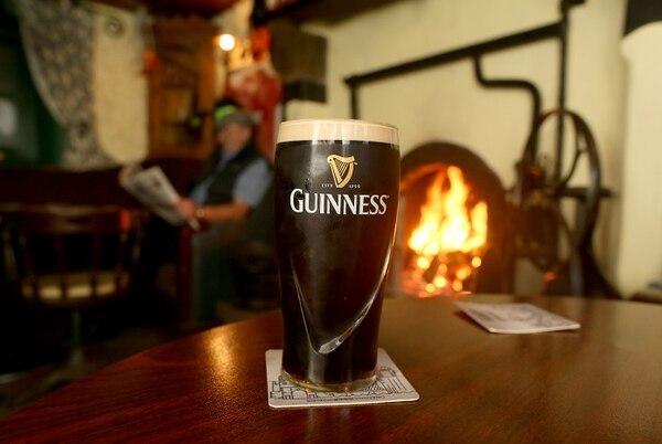 Guinness es una cerveza negra a base de granos tostados coronada por una espesa espuma cremosa. Fotografía: Paul Faith / AFP.