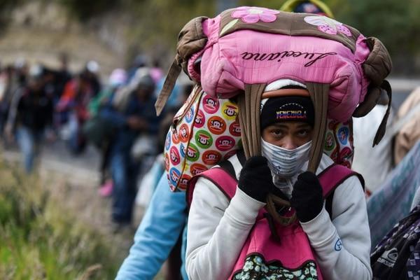 Una venezolana caminaba por la carretera Panamericana, a su paso por la ciudad ecuatoriana de Tulcan, rumbo a Perú, el martes 21 de agosto del 2018. Fotografía: AFP.