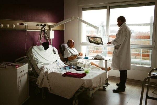 Sergei Orlov, de nacionalidad británica, habla con su médico mientras se recupera de una cirugía de rodilla en el Hospital Calais, en Calais, Francia. Este es uno de los pacientes del Reino Unido que cruza el Canal de la Mancha en busca de tratamientos médicos que no desean postergar.