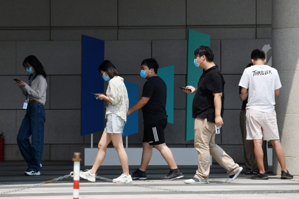 ByteDance staff walk past the company logo outside the ByteDance headquarters building in Beijing on July 8, 2020. - Video sharing app TikTok, which is owned by Chinese company ByteDance, announced on July 6 it was pulling out of Hong Kong, less than a week after a new national security law went into effect. (Photo by GREG BAKER / AFP)