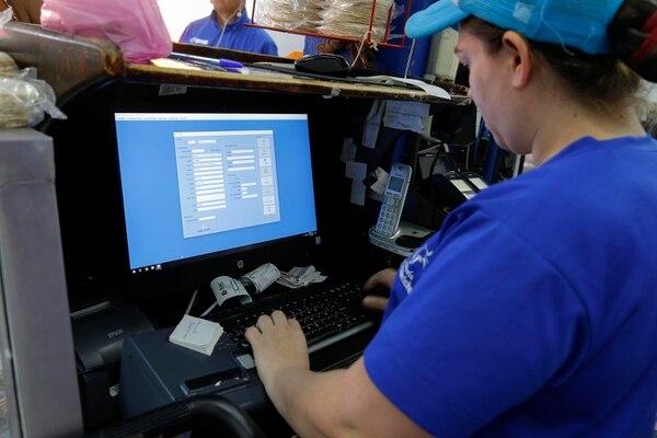 Mitcy Solís ingresa los datos de la cliente Jéssica Anchía, quien pidió la factura electrónica en la carincería El Chirriche, en Santa Ana. Fotografía: Mayela López.