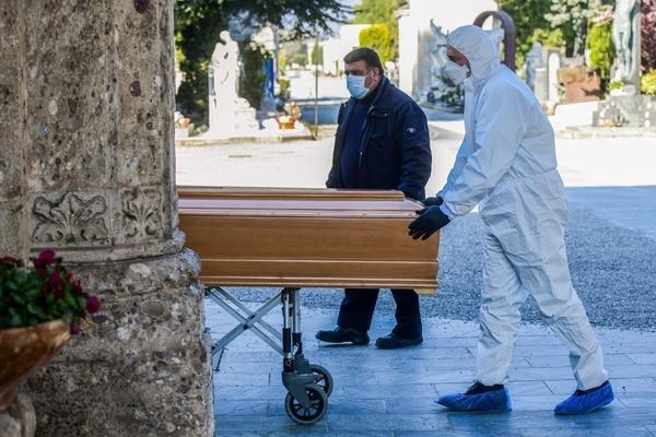 Un empresario de pompas fúnebres con una máscara facial y un mono descarga un ataúd de un coche fúnebre el 16 de marzo de 2020 en el cementerio monumental de Bérgamo, Lombardía, mientras se llevan a cabo entierros de personas que murieron por el nuevo coronavirus al ritmo de uno cada media hora. Foto: Piero Cruciatti / AFP