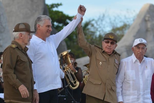 El presidente de Cuba, Miguel Díaz-Canel (segundo a la izquierda), y el exmandatario, Raúl Castro, alzan sus brazos durante la celebración del Día de la Revolución, en Bayamo, Cuba, el 26 de julio del 2019. Foto: AP