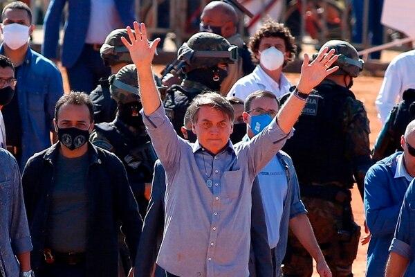 El presidente brasileño, Jair Bolsonaro, saluda a sus seguidores durante la inauguración de un hospital de campaña en Aguas Lindas, en el estado de Goiais, Brasil, el 5 de junio de 2020, en medio de la pandemia de coronavirus Covid-19. Fotografía: AFP.